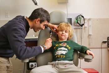 A doctor examines a small boy in a medical chair.