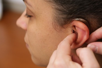 A girl is fitted with a hearing device.