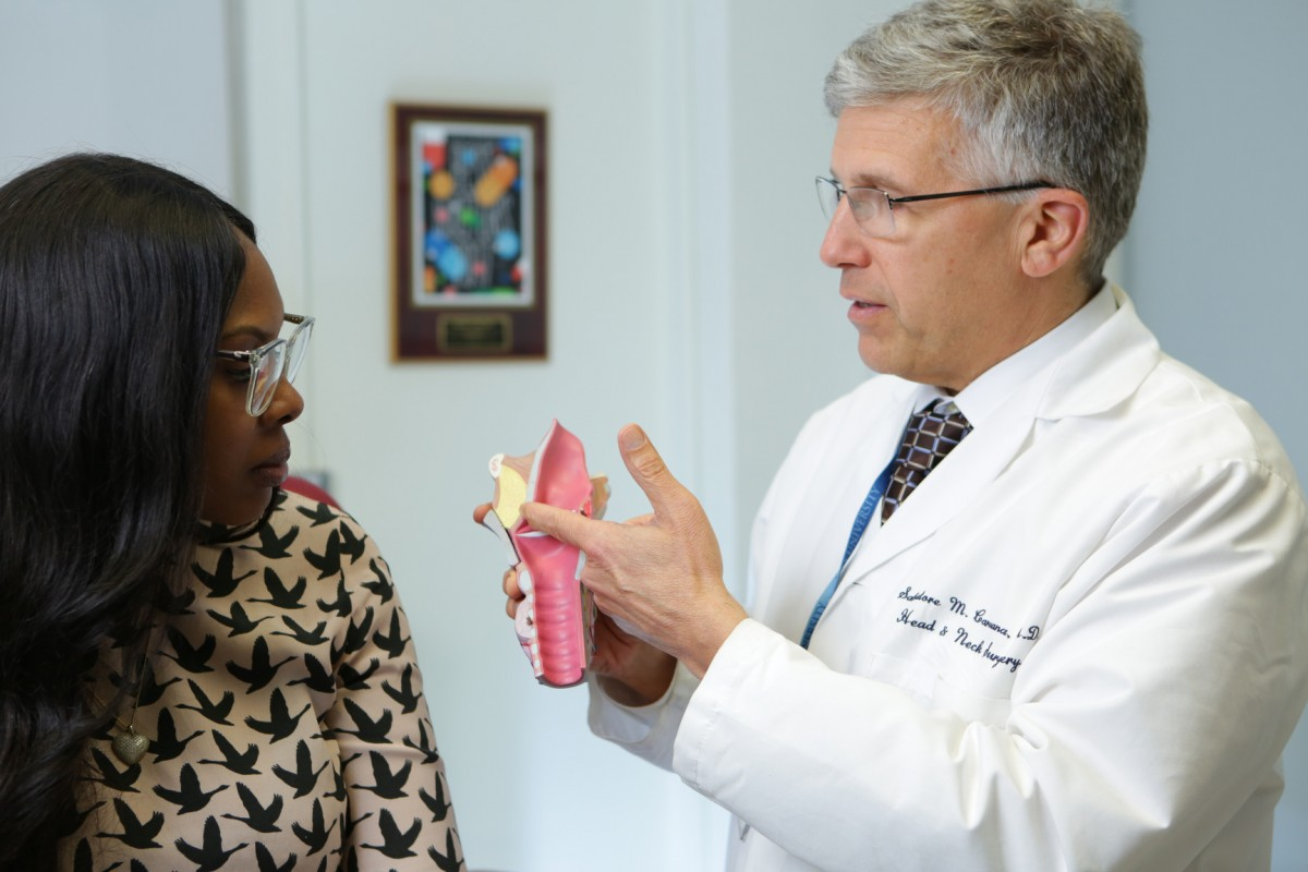 A doctor reviews an ear diagram with a patient.