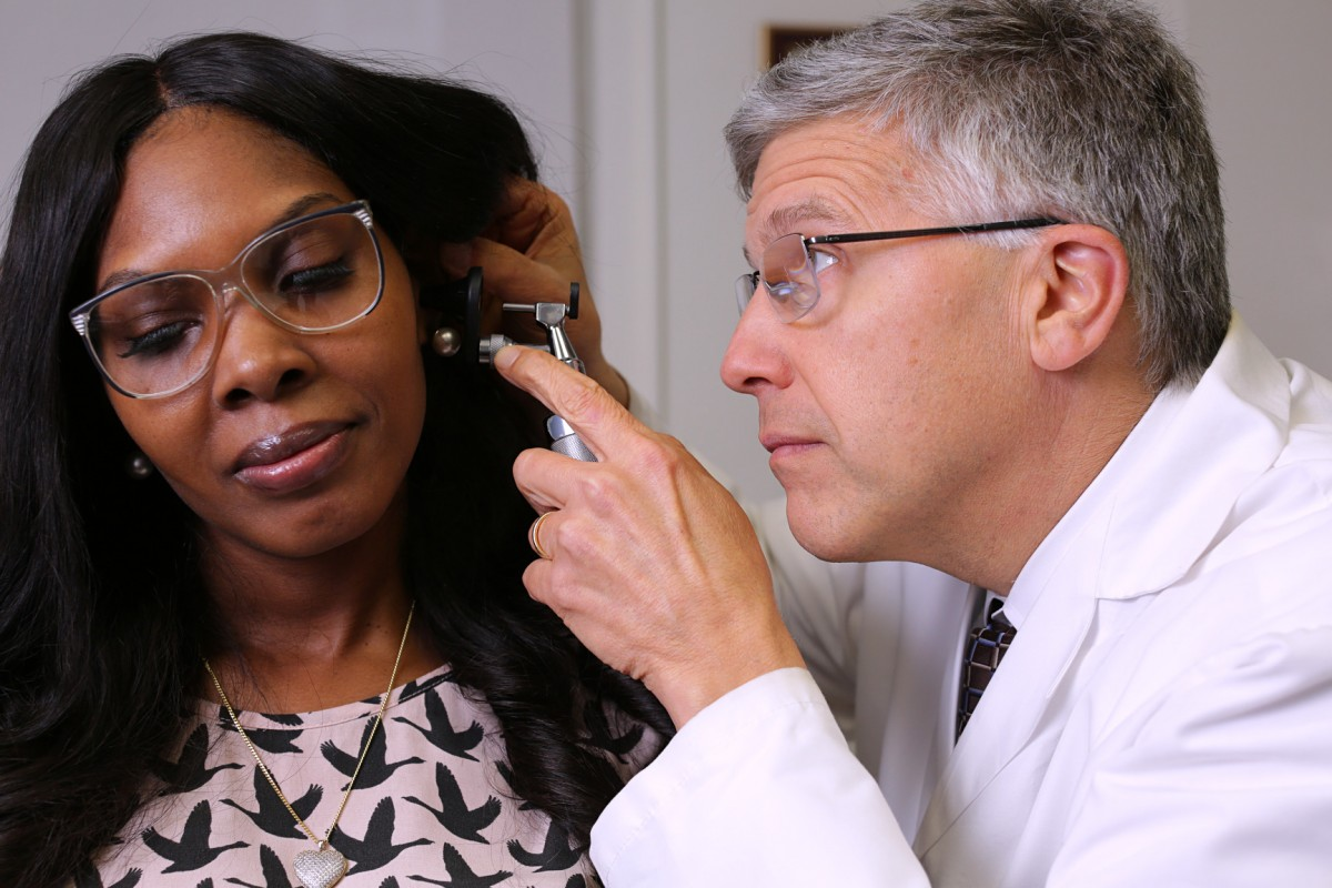 A doctor examines a patient's ear.