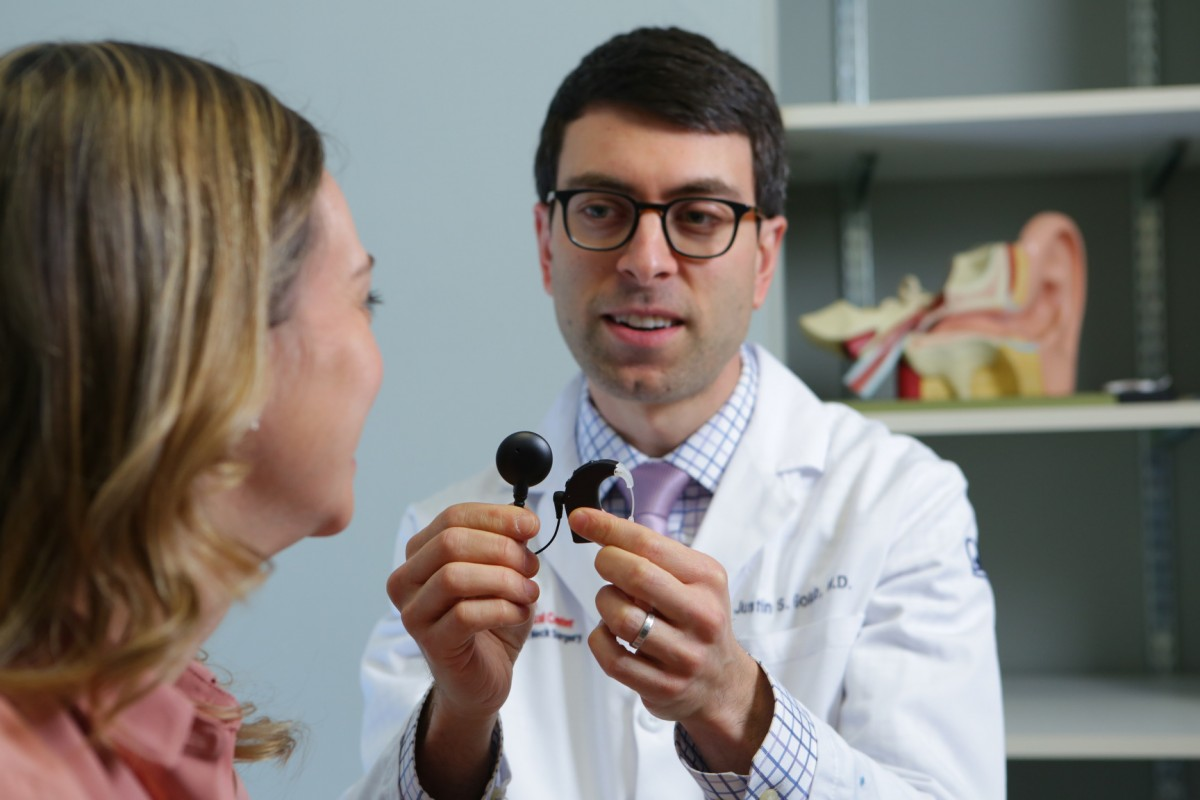A doctor talks to a patient while holding cochlear implants.