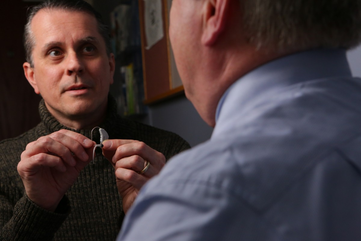 Dean Mancuso holds a hearing aid and talks to a patient.