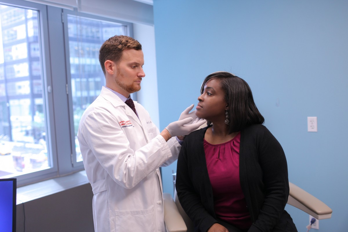 A doctor examines a patient's face.