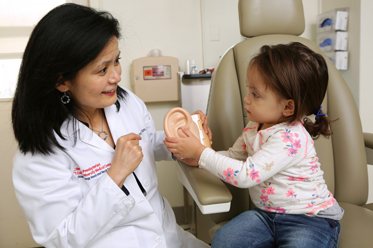 A doctor shows an ear diagram to a child.