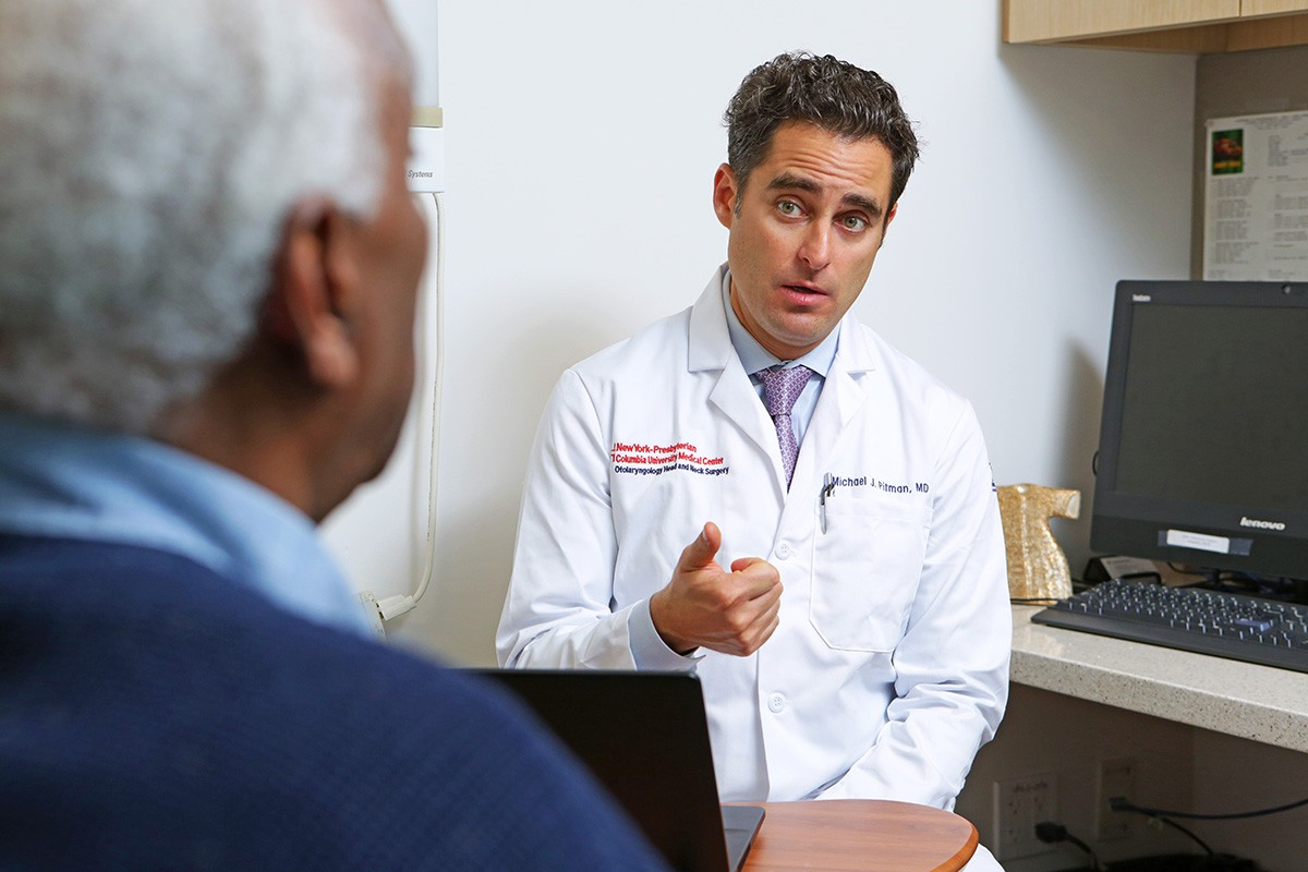 Dr. Michael Pitman speaking with a patient in an examination room.