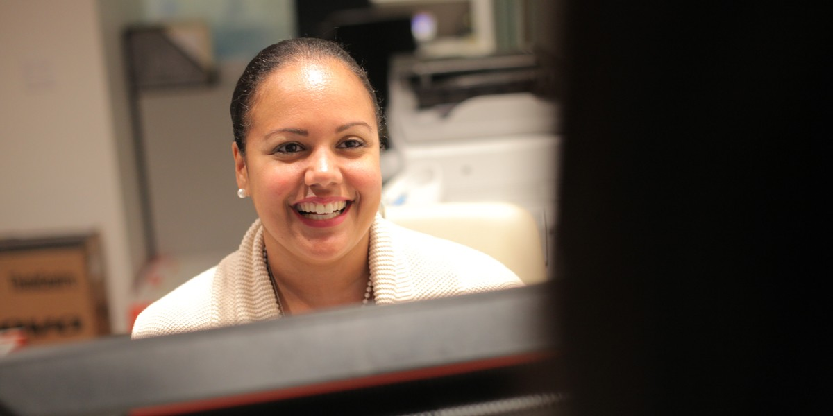 A woman smiling sitting at a reception desk.