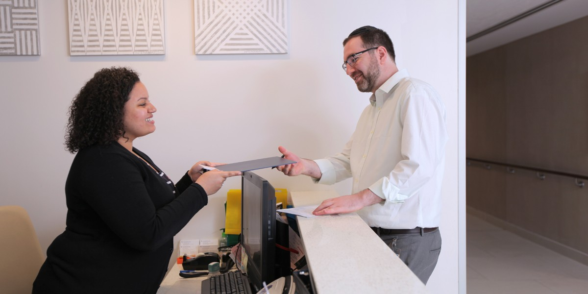 Staff member handing a patient forms to fill out at the front desk.